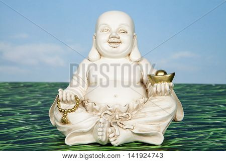 A good fortune Buddha holding a gold ingot and beads