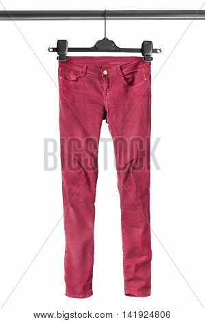 Red jeans on clothes rack isolated over white