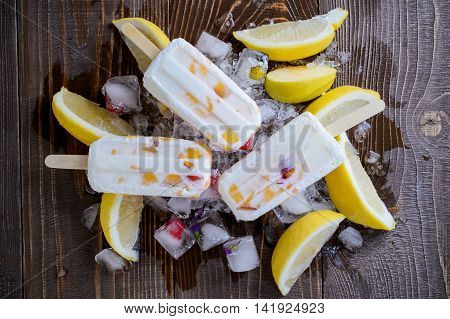 refreshing fruit popsicle on ice background with pieces of a lemon and apple