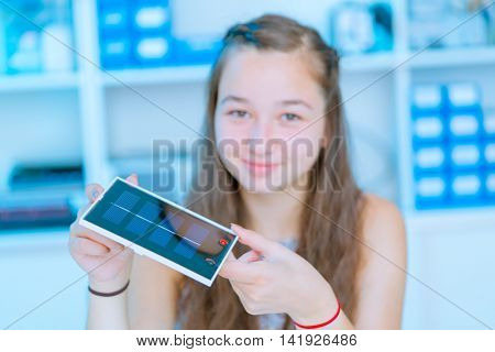 schoolgirl with solar cell in hand in physics classroom