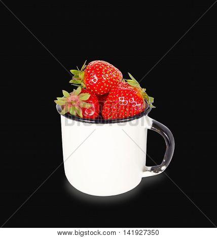 Fresh ripe red strawberries in enamel mug over black background
