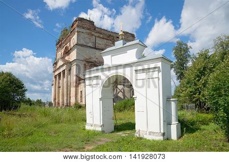 Ancient gate rural churchyard in the background of the abandoned Cathedral of St. Nicholas. The village of Nikolo-Korma, Yaroslavl region, Russia