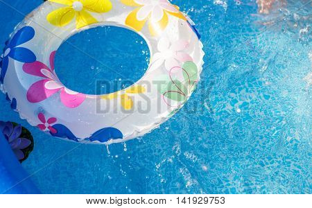 Inflatable swimming circle in open air pool in summer day.