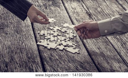 Two different hands of unidentifiable business people reaching for puzzle pieces from stack.