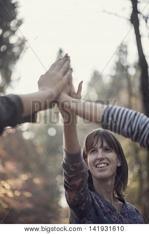 Group of people with focus to a smiling young woman giving a high fives gesture in a concept of teamwork and success.