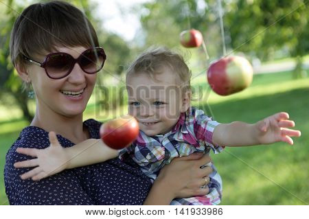 Boy catches an apple in a park
