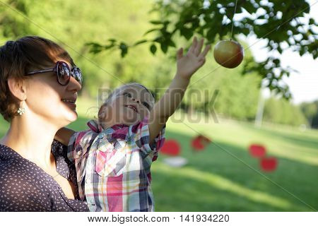Child catches an apple in a park