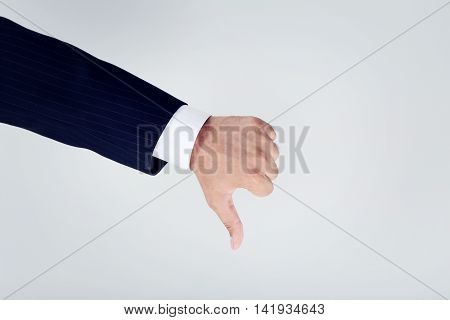 Businessman Gesturing Thumbs Down On Grey Background