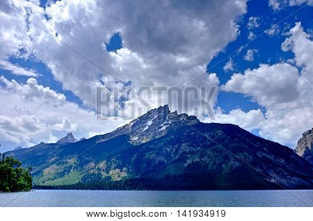 Impressive mountains with clouds by lake. Jenny Lake in Grand Tetons National park Jackson Wyoming.