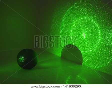 Dark ball with shadow on wall in green laser light