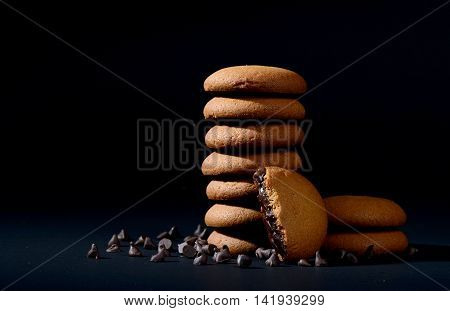BISCUITS - Stack of delicious cream biscuits, Biscuits filled with chocolate cream. Chocolate cream cookies. brown chocolate biscuits with cream filling on black background.