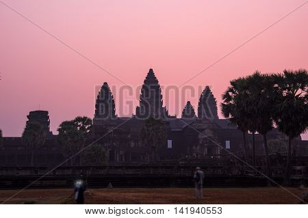 Tourists waiting for sunrise at Angkor Wat temple in Cambodia. Angkor Wat is the largest Hindu temple complex and religious monument in the world