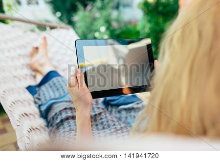 Woman using tablet computer while relaxing in a hammock.