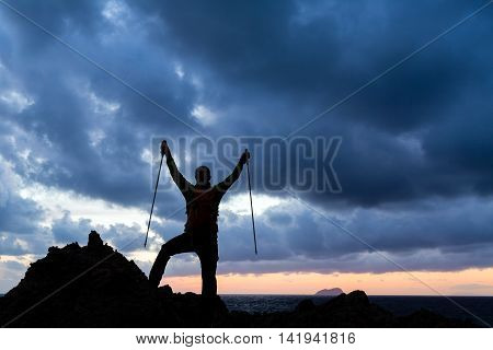 Success achievement trekking or hiking accomplishment. Business concept with man celebrating with arms up raised outstretched hiking climbing running outdoors. Motivation and inspiration in nature.