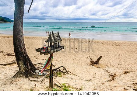 Phuket, Thailand - August 23, 2014: Beachside spirit house with offerings & strolling tourists at Kata beach, Phuket, southern Thailand