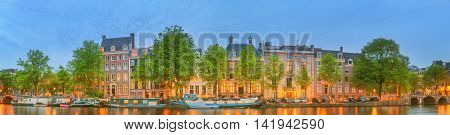 Panoramic view and cityscape of Amsterdam with boats, old buildings and Amstel river, Holland, Netherlands.