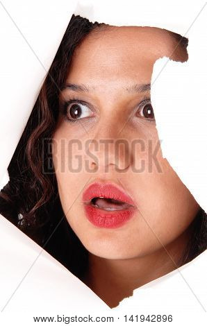 A lovely woman looking through a hole in a paper is shocked what she see's isolated for white background.
