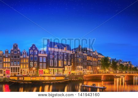 Amstel river, canals and night view of beautiful Amsterdam city. Netherlands.
