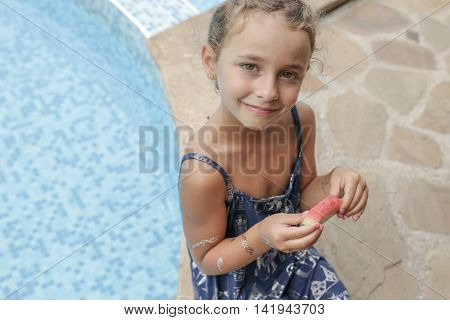 Blond curly girl eating fresh water melon