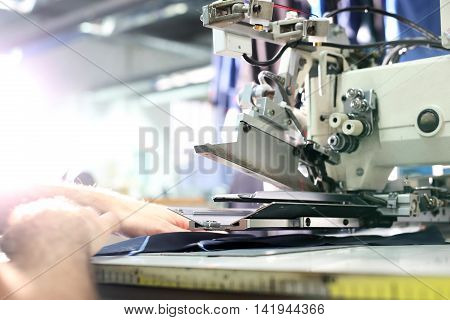The production plant, sewing clothes by seamstresses on the sewing machine