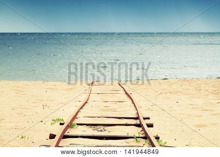 Old Rusted Railway Goes On Sandy Beach To Sea