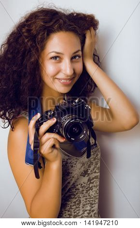 little cute teenage girl with curly hair holding camera, photographer taking a shot, lifestyle people concept
