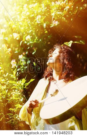 beautiful shamanic girl playing on shaman frame drum on background with leaves and flowers. solar light effect