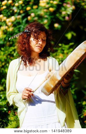 beautiful shamanic girl playing on shaman frame drum on background with leaves and flowers