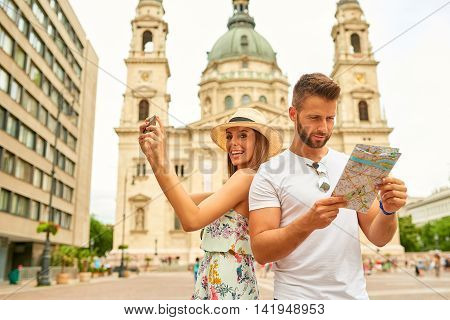 A handsome young man is feeling confused and looking at the map while his beautiful girlfriend is taking selfies at the St. Stephens Basilica in Budapest, Hungary.