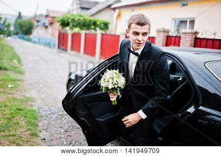 Stylish Young Groom Out Of The Wedding Car In Rainy Weather