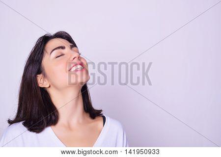 Closeup portrait of beautiful hispanic woman smiling. Latina model isolated over grey background.