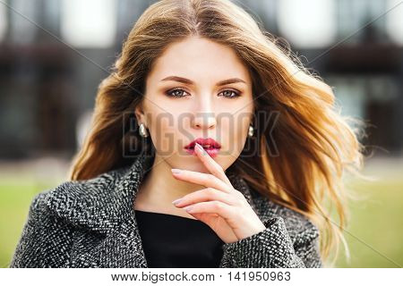 Portrait of attractive blonde woman with finger on lips concept of student show quiet silence secret gesture spring outdoors