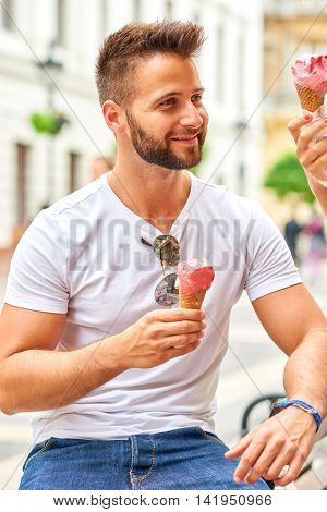 A handsome young man having an ice-cream on the street of Budapest, Hungary.