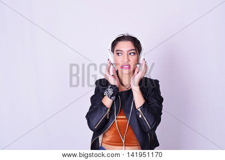 Music. Young hispanic woman listening to music with headphones. Playful woman isolated over grey background with fun expression.