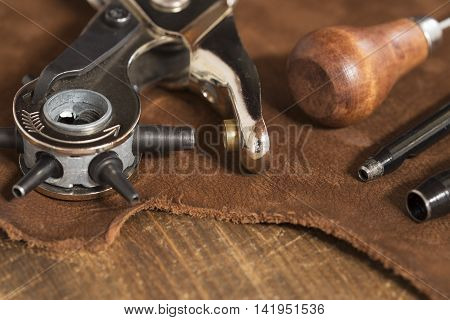 Leather craft tools on a brown leather background