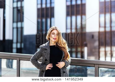 Pleasant modern attractive business young woman standing on office backgraund