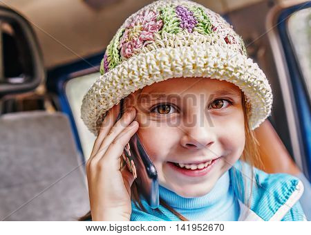 Little girl talking on mobile phone while sitting in the car.