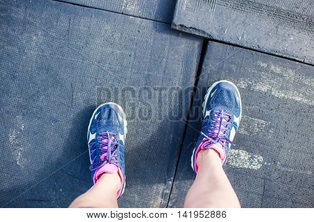 black old rubber floor of running track and sneakers. female legs in sneakers on the background of the destroyed rubber coating on running track of stadium.