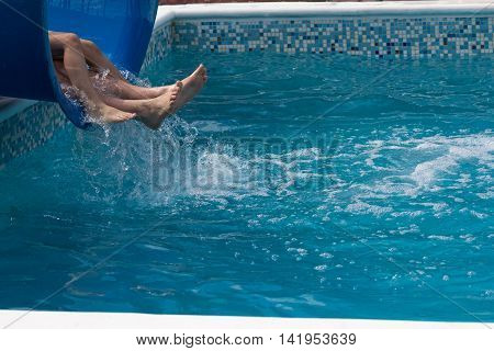 Legs of tourists descending on a slide in the pool. Recreation