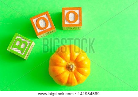 Boo spelled with alphabet blocks with pumpkin against a green background