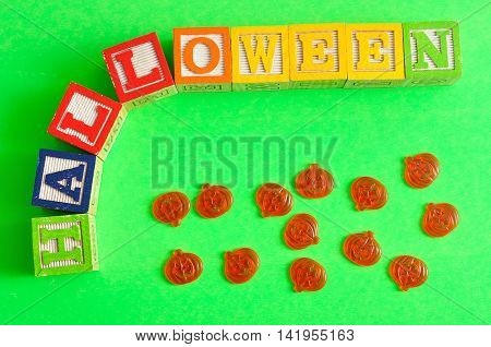 Halloween spelled with alphabet blocks with jack-o-lantern figures against a green background