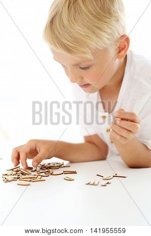 Children's fun. Preschooler boy arranges puzzle .