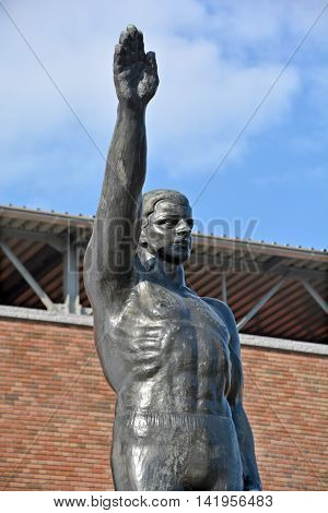 AMSTERDAM NETHERLANDS 02 10 2015: Sculpture by Gra Rueb Official Olympic Salute Stopped Being Popularly Used After WWII Due to Strongly Resembling the Heil Hitler Salute. In front the olympic stadium