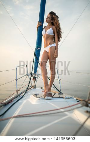 Slim girl stands sideways on the yacht in a white swimsuit and holds the mast on the background of the sea and the sky. She looks to the side. Outdoors. Vertical.