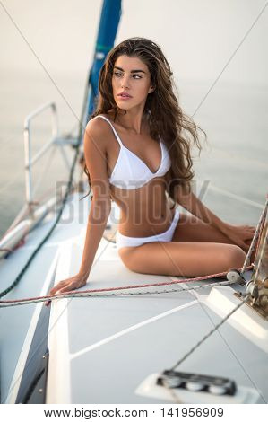 Model girl in a white swimsuit sits on the yacht and looks to the right with parted lips on the sea background. She leans on the right hand while left hand is on the left knee. Outdoors. Vertical.