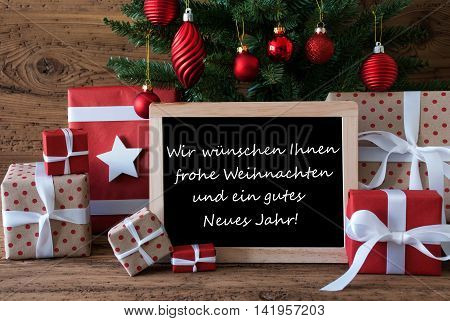 Colorful Christmas Card For Seasons Greetings. Christmas Tree With Red Balls. Gifts Or Presents In The Front Of Wooden Background. Chalkboard With German Text Frohe Weihnachten Und Ein Gutes Neues Jahr Means Merry Christmas And Happy New Year