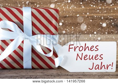Christmas Gift Or Present On Wooden Background With Snowflakes. Card For Seasons Greetings. White Ribbon With Bow. German Text Frohes Neues Jahr Means Happy New Year