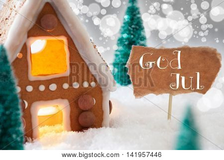 Gingerbread House In Snowy Scenery As Christmas Decoration. Trees And Candlelight For Romantic Atmosphere. Silver Background With Bokeh Effect. French Text God Jul Means Merry Christmas