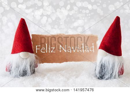 Christmas Greeting Card With Two Red Gnomes. Sparkling Bokeh Background With Snow. Spanish Text Felix Navidad Means Merry Christmas