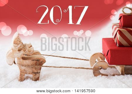 Moose Is Drawing A Sled With Red Gifts Or Presents In Snow. Christmas Card For Seasons Greetings. Red Christmassy Background With Bokeh Effect. English Text 2017 For Happy New Year